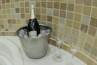 Banheira de hidromagassem e ao lado um balde de gelo com champanhe